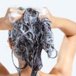 Woman washing hair with shampoo.